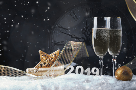 Two wine glasses with champagne, clock and Christmas ornaments on a black background with reflection