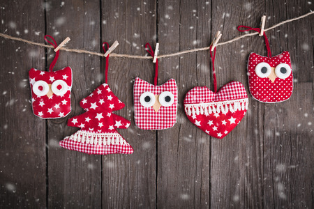 Christmas ornaments hanging on string over wooden background