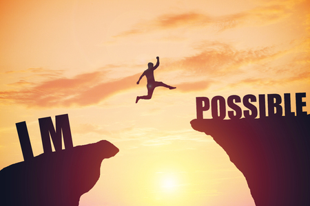 happy businessman jumping between two rocks with words: IM POSSIBLE