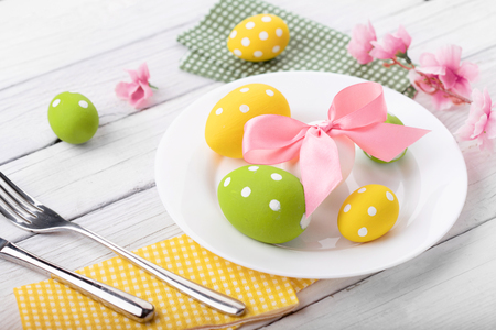 Easter table setting with spring flowers and cutlery.