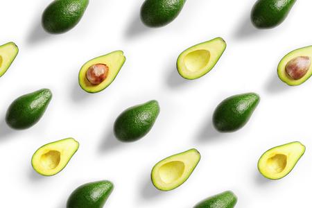 Plenty of fresh avocados on white background