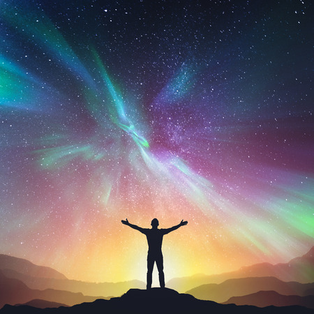 Silhouette of a standing young man with raised up arms on night stars and northern lights. Elements of this image furnished by NASA