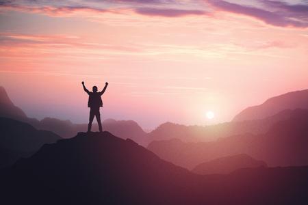 Personne de sexe masculin victorieux debout au sommet de la montagne avec les bras levés. Gagner et réussir