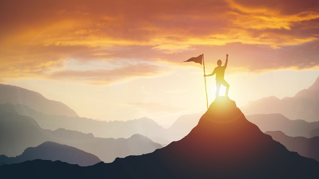 silhouette of businessman with flag on mountain top over sky and sun light background