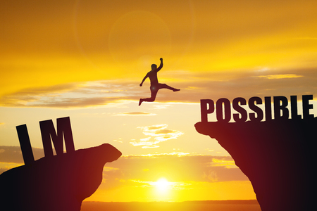 Man jumping over impossible or possible over cliff on sunset background Stockfoto