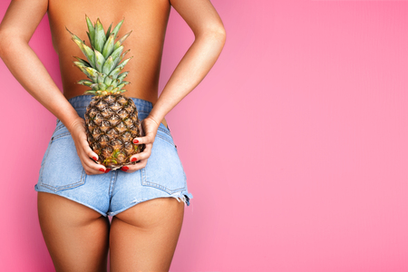 Young woman holding a pineapple in her hand on purple background. Sport and health concept.