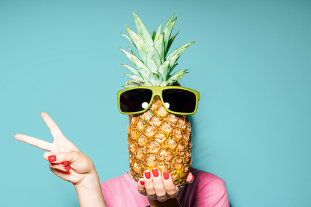 Woman and pineapple on her head standing over color background Stockfoto