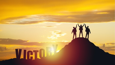 Silhouette of happy teamwork hold hands up as a business successful, business victory.