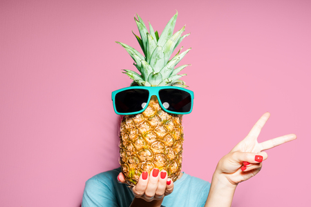 Fashion portrait woman and pineapple with sunglasses hiding head over color background