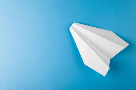 Flat lay of white paper plane and blank paper on pastel blue color background Stok Fotoğraf