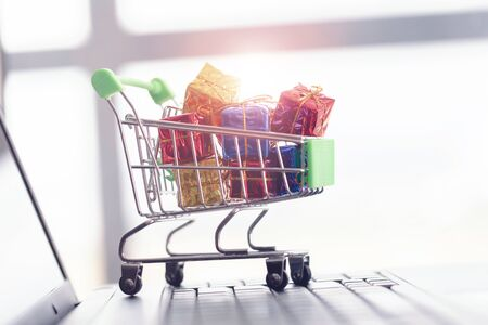 Gift boxes in a shopping cart on a laptop keyboard.