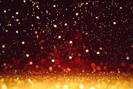 Scintillio dorato di Natale su rosso brillante. Sfondo di felice anno nuovo Archivio Fotografico