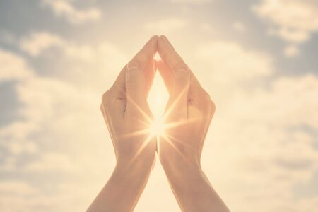 Woman hands holding the sun at dawn