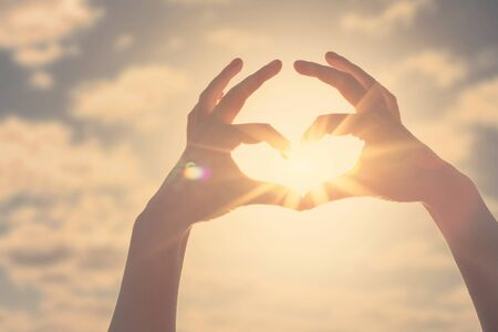 Hand heart shape silhouette made against the sun and sky of a sunrise or sunset. 免版税图像