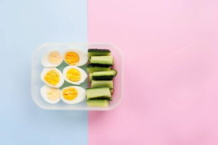 Eggs and cucumber in a container. Healthy eating concept. Top view. Flat lay 免版税图像