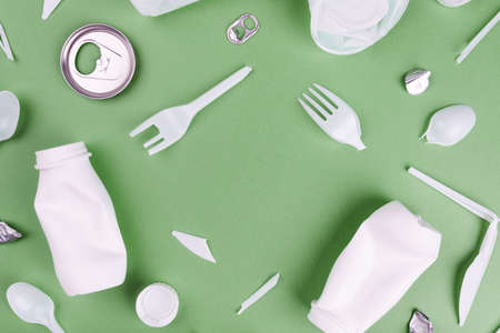 Eco plastic recycling concept. Single use plastics on green background.