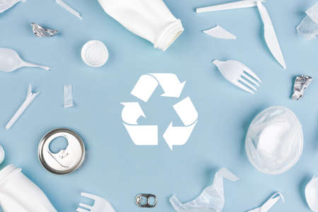 Top view of Different garbage materials with recycling symbol on blue background