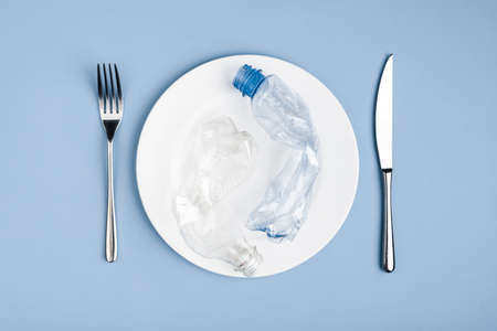 Top view of plastic waste garbage in the white plate, knife and fork