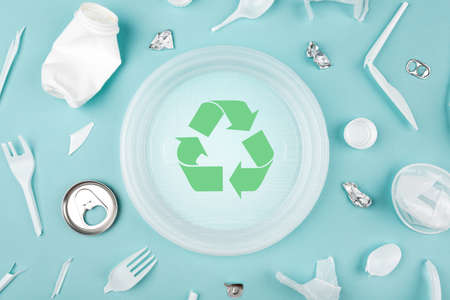 Different plastic trash and garbage recycling sign on a blue background, top view. The concept of saving the planet, the separation of garbage.