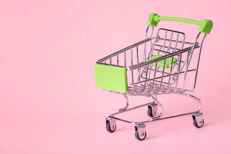 Empty top view mini pink shopping cart or trolley shopping on pink background