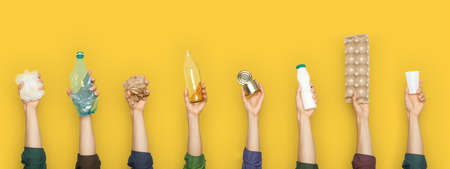 Partial view of group of people holding various types of garbage on yellow background 免版税图像