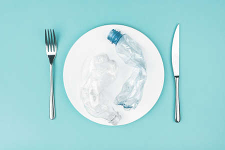 Plate with plastic bottles on blue background.