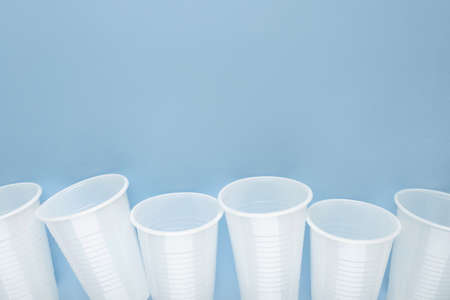 White plastic empty cups laid out in a row on blue background.