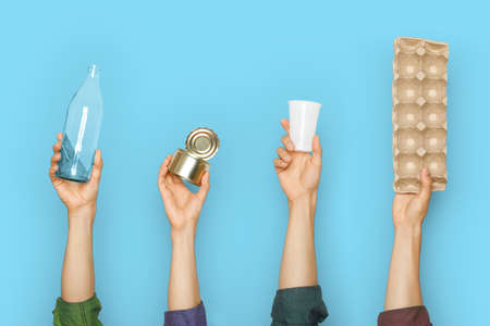 Different types of waste in the hands on a blue background. Stock fotó