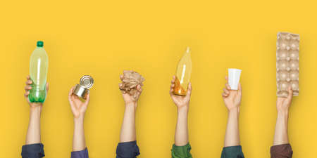 Hands hold trash on a yellow background. 免版税图像