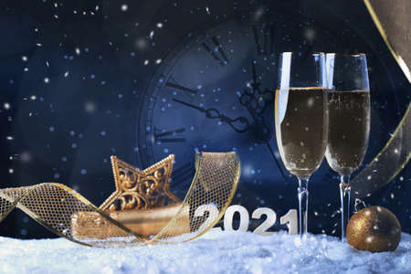 Two glasses of champagne with golden ribbon, star and ball with snow. Night of celebration concept 免版税图像