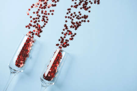 Champagne glass with red confetti on blue background. Flat lay of Celebration.