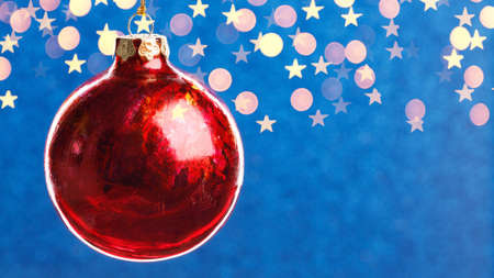 Christmas red ball on blue background with golden lights, copy space