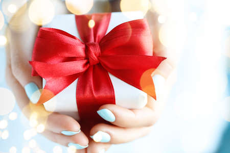 Woman holding a gift box with red bow in a gesture of giving.