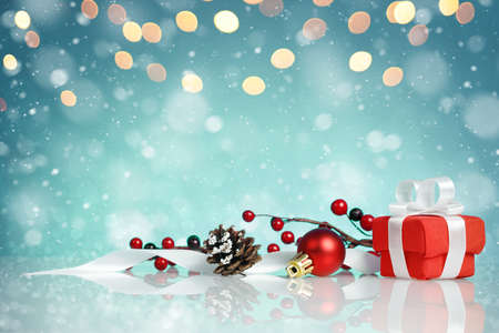Red gift box with christmas decorations on blue background with copy space.