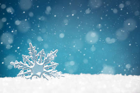 Transparent shape of a snowflake in a snowdrift on a blue background, copy space