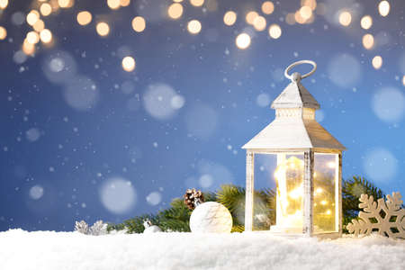 White lantern in snow, with yellow candle light and christmas decorations on blue background