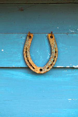 Antique rusty horseshoe on blue wooden farm door. Stock Photo