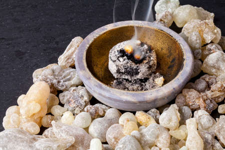 Frankincense burning on a hot coal. Frankincense is an aromatic resin, used for religious rites, incense and perfumes. Archivio Fotografico