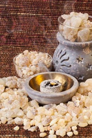 Frankincense burning on a hot coal. Frankincense is an aromatic resin, used for religious rites, incense and perfumes. Imagens