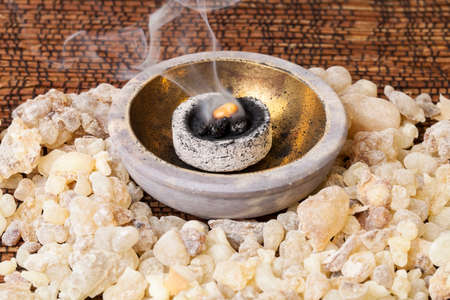 Frankincense burning on a hot coal. Frankincense is an aromatic resin, used for religious rites, incense and perfumes. 写真素材