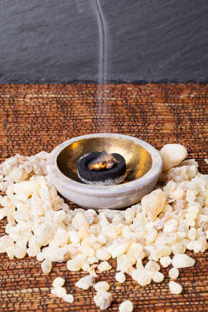 rites: Frankincense burning on a hot coal. Frankincense is an aromatic resin, used for religious rites, incense and perfumes. Stock Photo