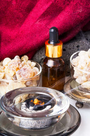 sacra: Bottle with organic essential aroma oil from Frankincense tree (Boswellia sacra) tree resin and Frankincense incense. Stock Photo