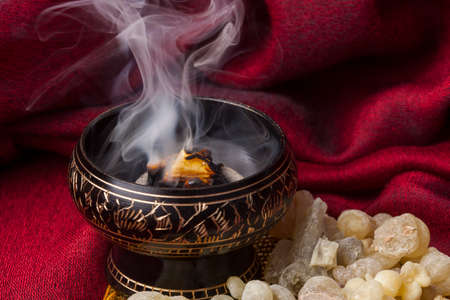 Frankincense burning on a hot coal. Frankincense is an aromatic resin, used for religious rites, incense and perfumes. Stockfoto