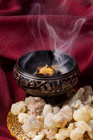 Frankincense burning on a hot coal. Frankincense is an aromatic resin, used for religious rites, incense and perfumes. Banque d'images