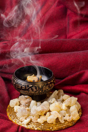 Frankincense burning on a hot coal. Frankincense is an aromatic resin, used for religious rites, incense and perfumes. Stock Photo