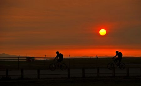 A pair of cyclists enjoy the summer with an evening ride during a beautiful sunset.