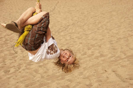 A stylish young boy having fun swinging on a rope at a park.