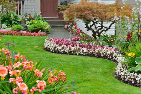 Landscaped home garden with a variety of annuals and perrenials in full bloom.