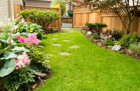 wooden fence: Back yard path leads past garden in bloom during transition from spring to summer.