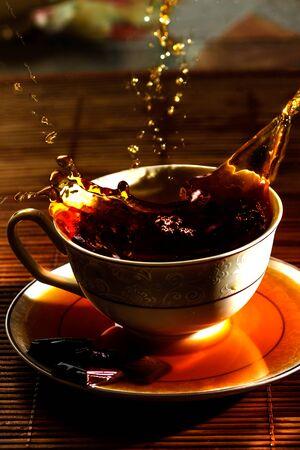 A splash of tea poured into a cup on a saucer. High quality photo Zdjęcie Seryjne
